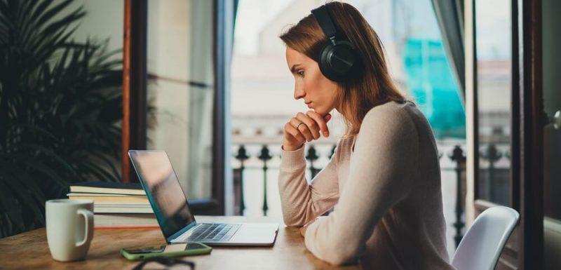 Kvinna i profil sittandes med headset framför en laptop